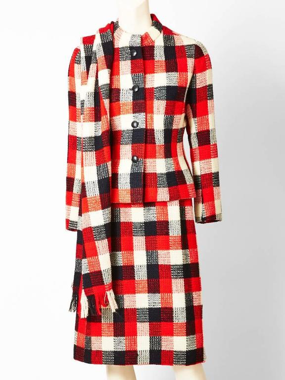 "Givenchy Couture, ""Buffalo"" plaid, wool suit with scarf in ivory, red and black. Jacket is collarless, slightly fitted, and ends at the hip. Skirt is straight."