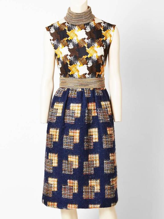 Ronald Amey,  mohair, wool and knit dress and jacket ensemble. Dress is sleeveless with a patterned silk bodice that  reflects the navy wool tweed pattern of the jacket and skirt. The skirt of the dress is slightly gathered. The waist band is a wool