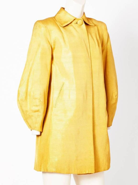 Dior-New York, gold ottoman 3/4 evening coat c. 1960's. Coat is narrow at the underarm and begins to flair into a trapeze shape. Sleeves are full and narrows at the wrist.