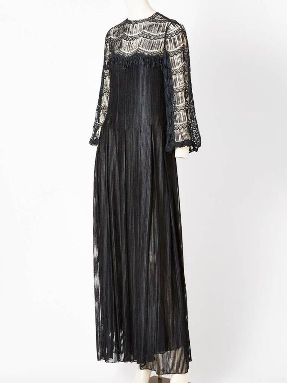 James Galanos gown, having a neckline and sleeve with open work and lace detail. Bodice is semi fitted with the skirt having box pleats that start at the hem and extends to the hem. Neckline and sleeves expose the skin, where the bodice and hem are