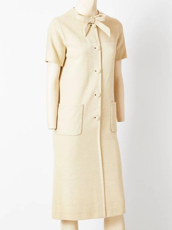Norman Norell, oatmeal tone, wool knit, sheath, having buttons closing down the middle front, short sleeves, a rolled neck with a front bow and visible deep patch pockets.