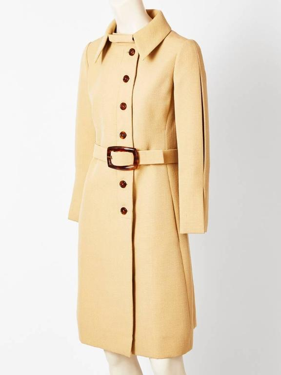Galanos, camel tone, belted wool coat, having a pointed collar, slim silhouette, and faux tortoise belt buckle and buttons.