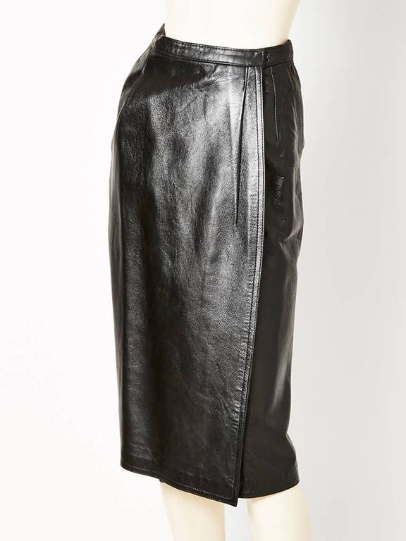 Yves Saint Laurent Leather wrap skirt C. 1970's having a slightly A line silhouette. ( label missing: this skirt was part of a suit which we decided to sell separately. ) Please note that the leather is supple but heavy.