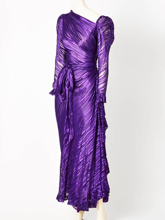 Yves Saint Laurent, purple, bias cut, asymmetrical neckline, long sleeve gown, having a self belt that ties at the waist.