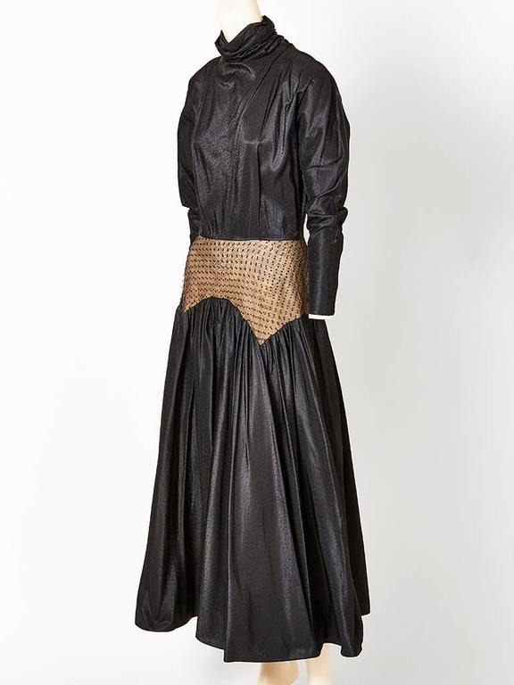 Geoffrey Beene, black silk jacquard dress, having a soft funnel neck that is ruched at the sides. Sleeves are raglan, that get narrow at the wrist.There is a point d'esprit pannel  that sits at the waist and hip over a nude tone taffeta. Skirt of