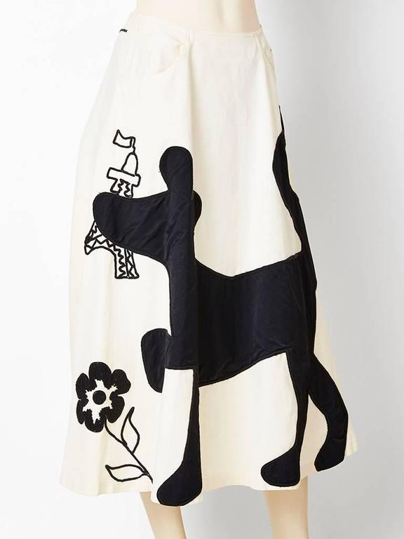 Jean Charles de Castelbajac, whimsical midi, skirt in an ivory cotton canvas having black appiques and embroidery depicting a dog, Eiffel tower and flowers. Skirt has a full a line shape with hip pockets.