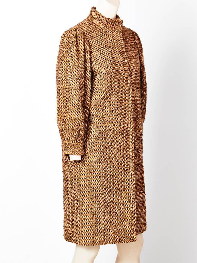 Galanos, mustard and brown tweed, wool coat having a mandarin collar, blouson sleeves with gathering at the shoulder, hidden button closures, and patch pockets. Coat has a slim silhouette.