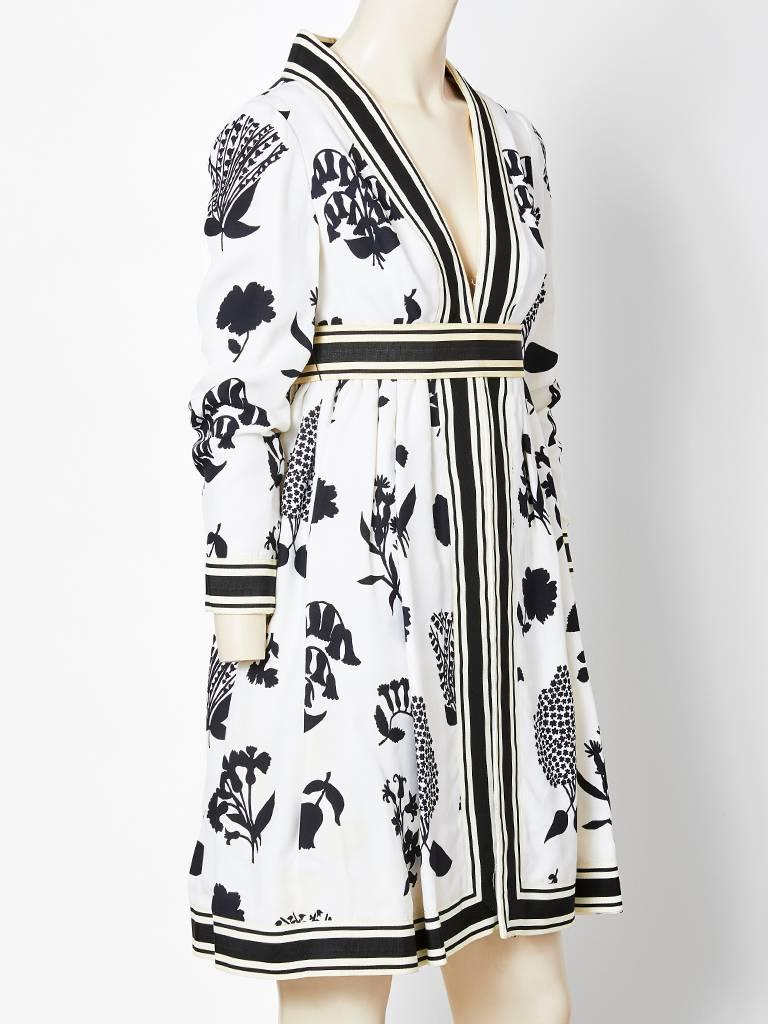 Geoffrey Beene black and white graphic floral pattern, empire waist day dress, C. late  60's . Dress has a deep V neckline with hidden closure down the front. Striped black and white gross grain ribbon embellish the dress along the neck, front  cuff