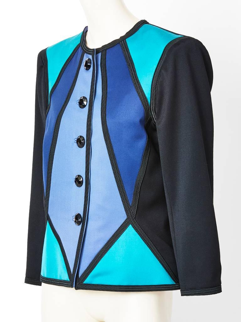 Yves Saint Laurent, Rive Gauche, duchess satin, color block, fitted dinner jacket in blue tones. Jacket is made of geometric satin fabric pieced together with black braid detail. There are black faceted glass buttons closures.  Back of jacket is