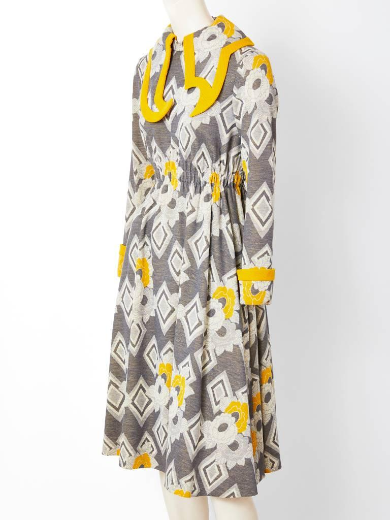 Ronald Amey, wool knit,  grey and mustard, patterned, day dress  having an asymmetric large cut out collar  trimmed  in a mustard tone. Back zipper closure with an elastic waist. C. 1970's.