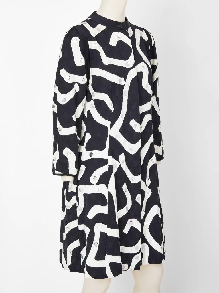 Geoffrey Beene, black and white, graphic pattern, textured, heavy cotton damask coat, having silver paiettes embellishment. Coat has a semi fitted silhouette with a banded collar in black. Can be worn as a dress.