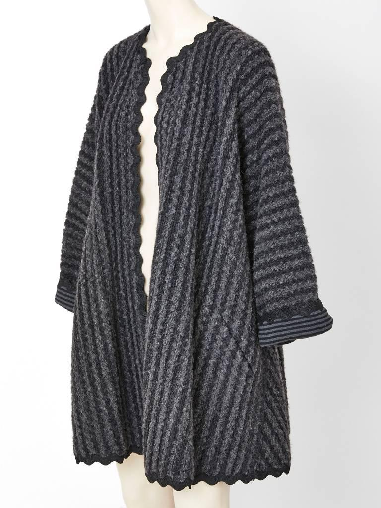 Geoffrey Beene, wool knit and mohair ribbed, grey kimono style, swing coat having a grey and black striped interior and black large ric rac trim.