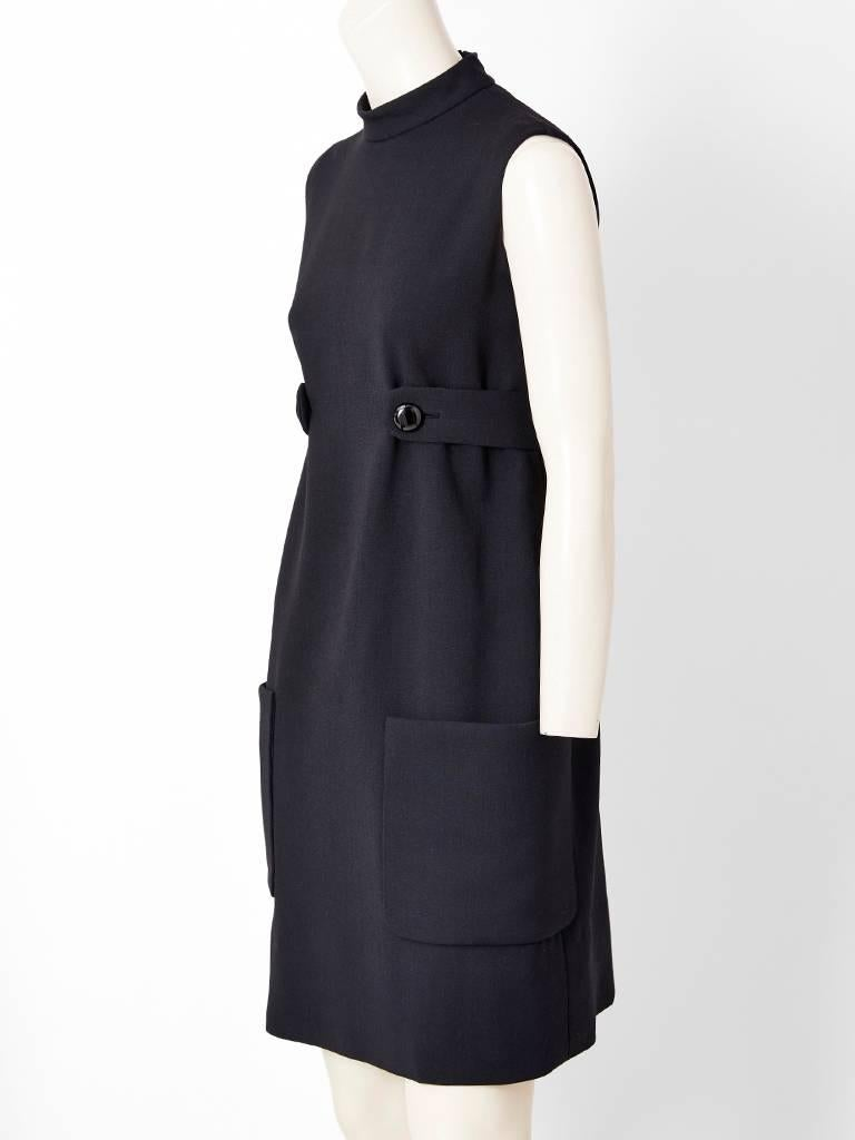 Classic Norell, black wool, sleeveless sheath, having a high neckline, slightly empire waist with a half belt attached by buttons and low placed, deep patch pockets detail. ( Missing Label ).