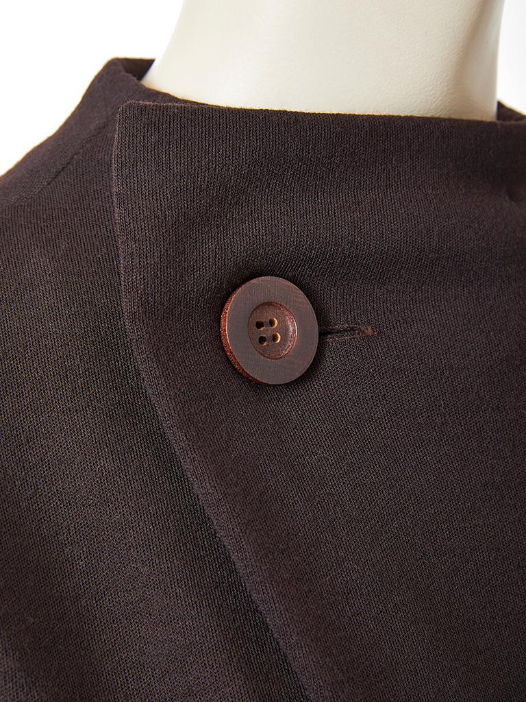 Geoffrey Beene, wool knit, fitted day dress, having cap sleeves and an off center, curved closing at the neckline, embellished by a singular large wood button closure.