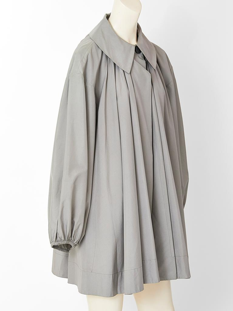 Yves Saint Laurent, grey, silk taffeta swing jacket, having a pointed collar that fastens at the neck. Balloon sleeves, have elastic at the wrist. Jacket gathers all around at the shoulder, front and back creating volume and movement.