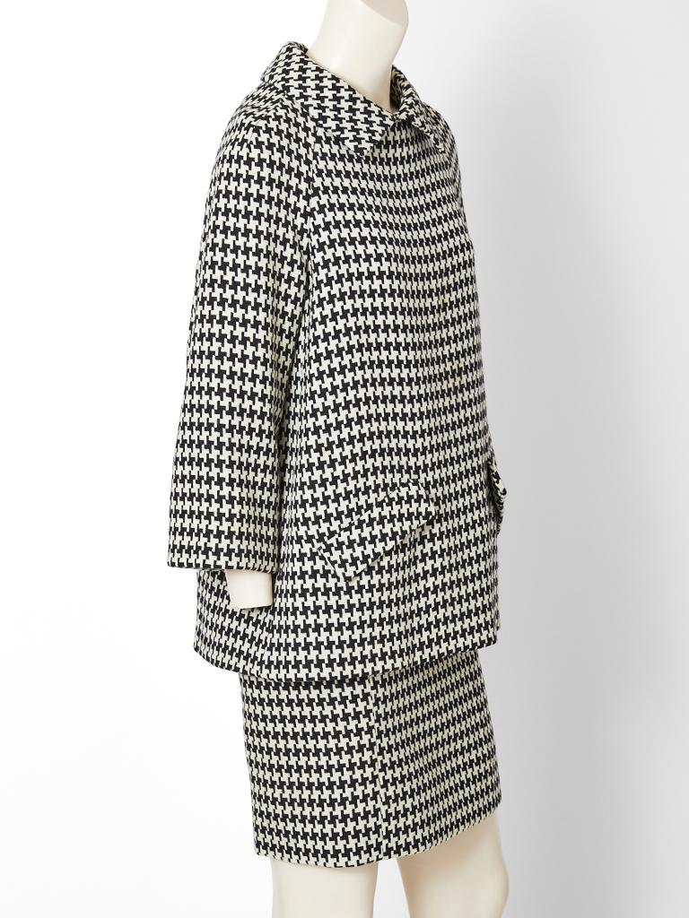 Geoffrey Beene, black and white, large scale, wool, houndstooth pattern, tunic and skirt ensemble. Tunic has an A line silhouette, having a pointed collar, lowly placed flap pockets and center back button closures. Matching pencil skirt ends above