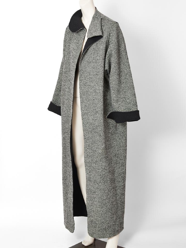 Geoffrey Beene, double face wool, straight line, maxi coat, having a black and white tweed exterior, and a black wool interior. There is a stand up collar that falls softly at the chin. Sleeves can be cuffed at the wrist to expose the black interior.