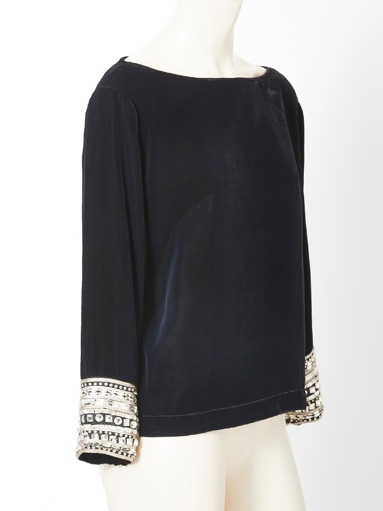Yves Saint Laurent, RIve Gauche, black velvet evening top having a bateau neckline and  long sleeves embellished at the wrists, with faceted rhinestones of various sizes and shapes.   Designer: