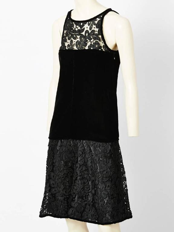 Yves Saint Laurent, black, velvet and lace cocktail dress. Collarless, sleeveless, with a lace bodice ending above the bust. The middle section is velvet, fitted at the bodice, waist, and hip, ending at the upper thigh. From the upper thigh to the