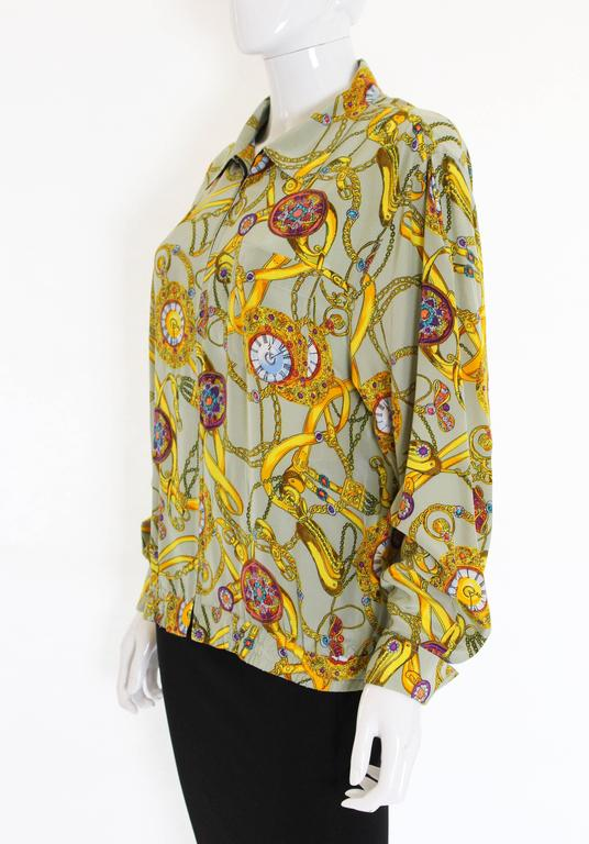 A wonderful silk blouson jacket by French designer Pierre Cardin. In a sage green silk with an interesting print of clocks and chains, this jacket has a pocket on the left hand side and an interesting pleat detail on the back. There is a zip