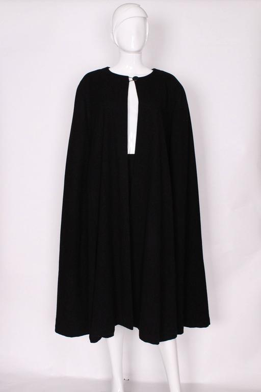 A stunning black wool cape by Yves Saint Laurent, Rive Gauche.The cape is collarless, with a single button fastening at the neck.