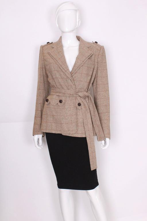 A great jacket for Fall from Yves Saint Laurent, Rive Gauche .The jacket is in a silk/linen mix, in a light brown speckled fabric with tan lines.It has one breast pocket on the left hand side and two pockets at waist level. The buttons are covered