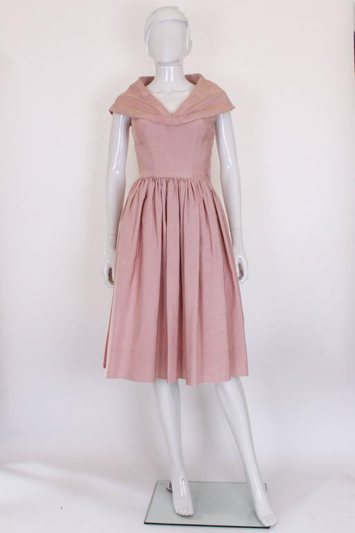 This is a stunning 1950s in a soft dusty pink. The fabric is a ribbed, structured silk that helps to shape the dress. The skirt is densely gathered around the waist so that the skirt has lots of volume. The top is very fitted and has a large shawl