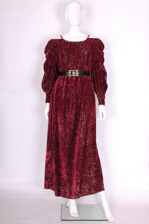 A glamorous gown by Christian Dior Boutique, Paris. In a wonderful burgundy and gold ribbed fabric , this gown can be worn on or off the shoulder. There is a 17'' slit on the left hand side, 2 pockets at hip level, and a wide 3 button cuff.