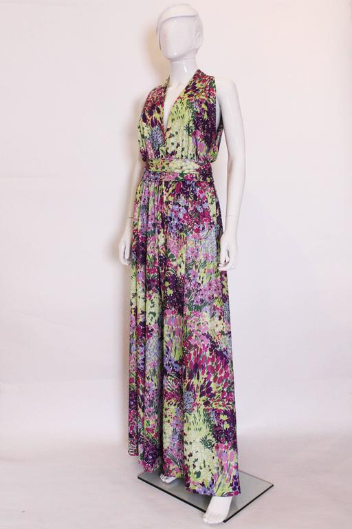Stunning for Summer. This floral gown by British firm Berketx is a real head turner. In a vivid mix of colours , greens, lilac,  purple and burgundy, it hangs beautifuly. The dress is sleevless with a v neckline,  a button fastening at the neck, and