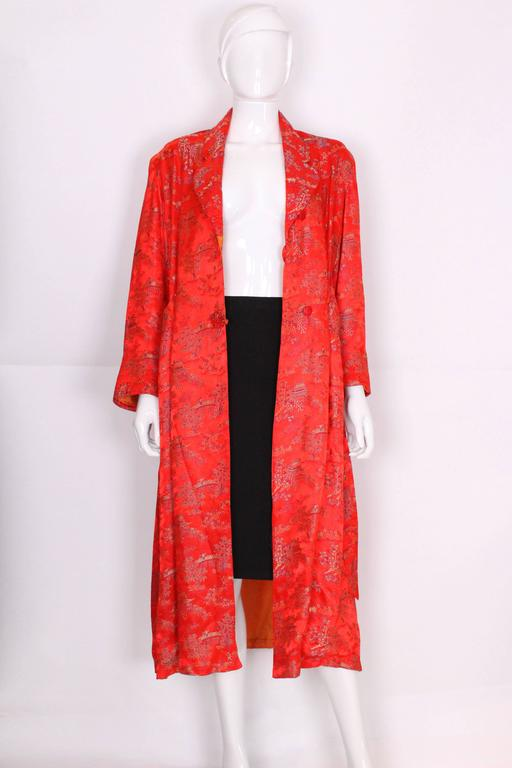 This dressing gown by Cherry is in a wonderful red with Chinese detail with an orange lining. The collar is cut away with quilted detail, that is also found on the cuffs and pockets. The gown has shoulder pads, a self tie belt and an internal tie