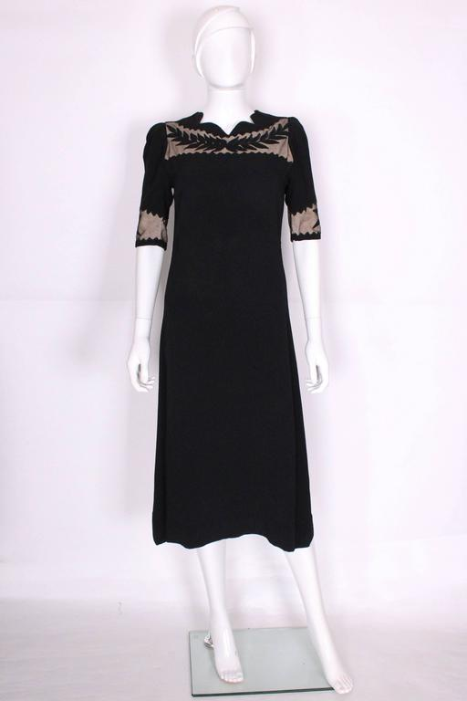 This is a charming and chic dress from the 1940's with some great detailing. It's made of a black crepe with nude coloured fabric in the cutout sections. There are black leaf applique details on top of the nude cutouts on the sleeves and bust. The