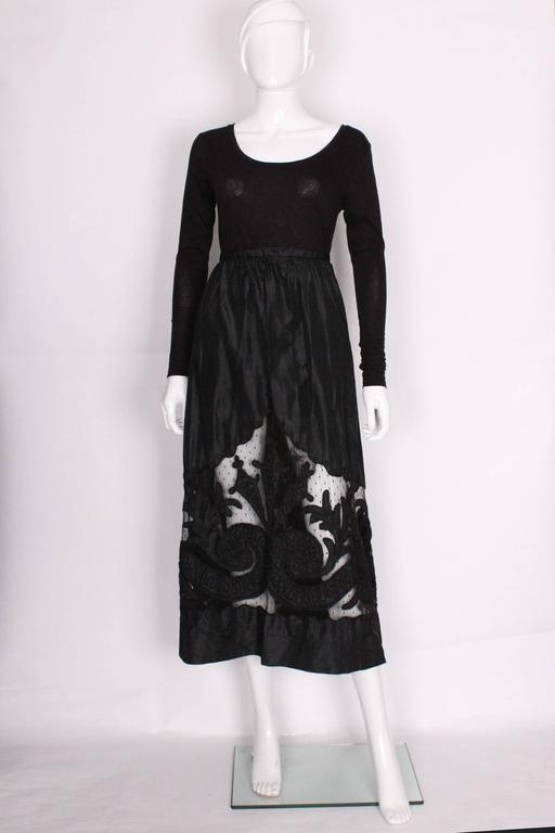 This is a really beautiful, black skirt from the Edwardian era. It's made of a heavy silk that has a slight shine to it and has a large cut out panel at the bottom that is filled in with netting. On top of the netting there are decorative panels of
