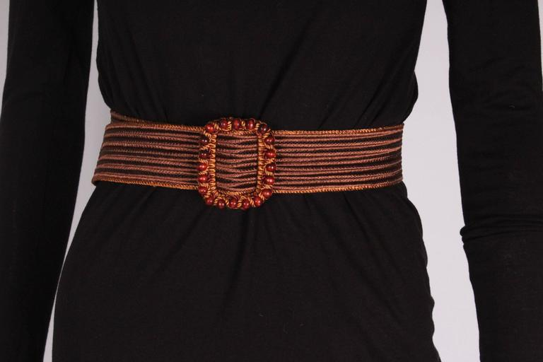A great belt for Spring, in a dark brown woven silk with tan edging. The buck has bead detail. The belt pulls through , so can fit most sizes. Length 34'' , height 2''