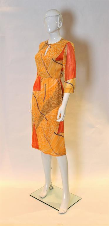A great dress by Chanel Creations. In a multi colour silk chiffon,shades of orange,olive, blue , and aubergine.The dress has a key hole neckline, side zip and elbow length sleeves. The top half is lined in silk chiffon and the bottom in sik.