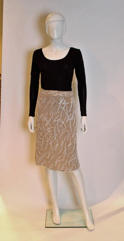 A great skirt by Tomasz Starzewski. In coffee coloured silk,inside and out, the skirt is covered in white beads and sequins.The skirt has a central back zip.