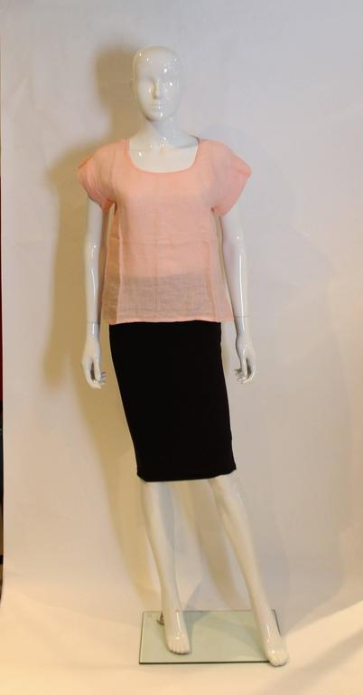 A pretty pink linen top by Yves Saint Laurent Rive Gauche.The top has a deep round neckline, and cap sleeves.