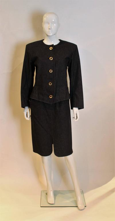 A great suit for Spring. This black skirt suit  has a round necked jacket with 5 button front opening. It has 3 buttons on each cuff, one breast pocket on the left hand side and 2 pockets at hip leval. The skirt has a zip opening on the left hand