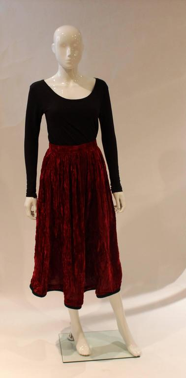 A red velvet skirt  by Yves Saint Laurent from his Russian collection. The skirt is in red velvet with black braid at the hem. It has a zip and pocket on the left hand side.