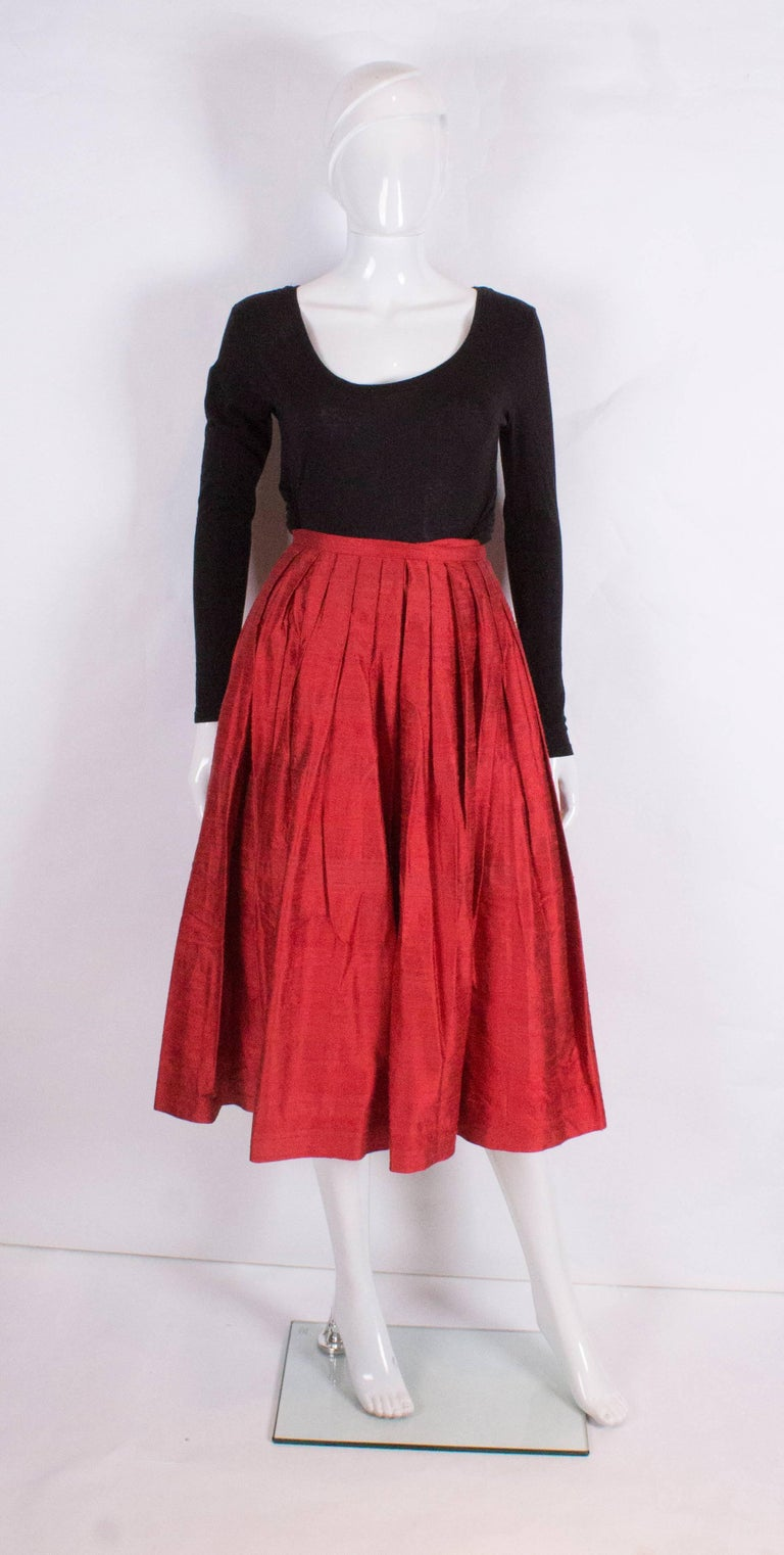A great skirt by Caroline Charles. In a tomato red raw silk, the skirt is gathered and  pleated from the waist band .The skirt is fully lined and has a 2 1/2 hem.