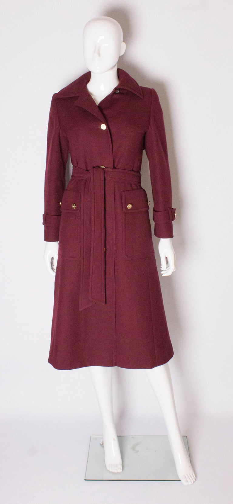 A great coat for Autumn /Winter by Aquascutum for Harrods. In a burgundy colour wool, the coat has a 4 button opening , two large pockets on the front and a self tie belt. It is fully lined.