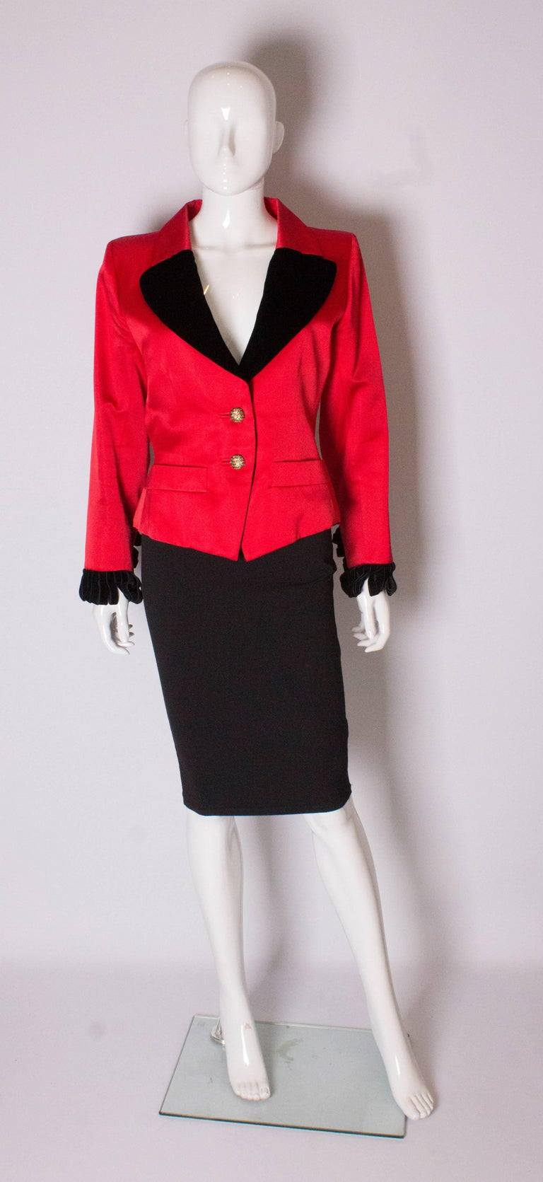 A red evening jacket by Yves Saint Laurent Rive Gauche. The red jacket has a red and black collar with black velvet frill cuffs and velvet ties at the back. It has a two button opening and pockets at waist level.