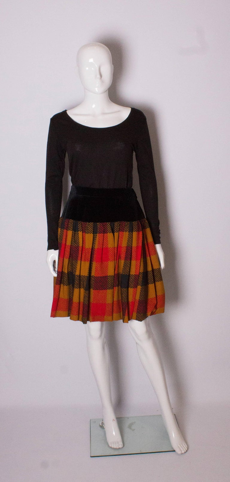 A great skirt by Yves Saint Laurent, Rve Gauche line. The skirt has a black velvet panel below the waist and then a gathered  caramel check wool section. The skirt has a 6'' hem and can be let down if required. The skirt is fully lined and has