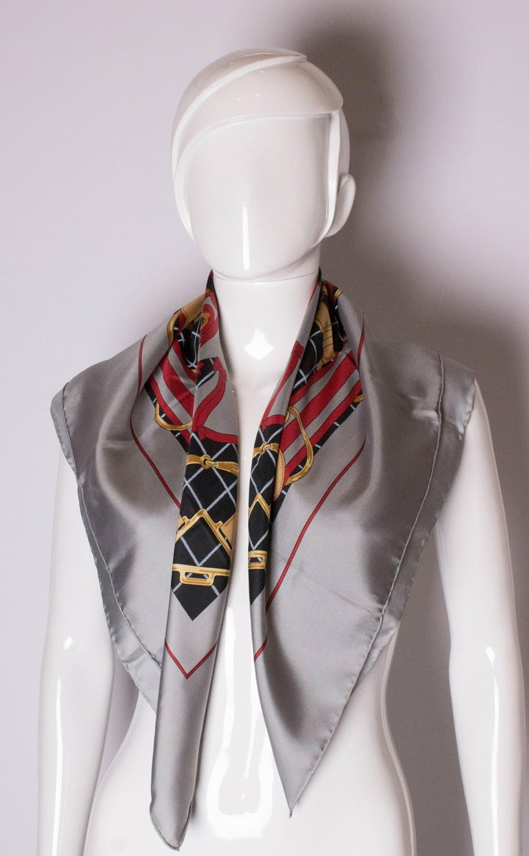 A chic silk scarf by Hermes. This one is 'Selliers', and has grey border with a gold, red and blue print. 35'' square.