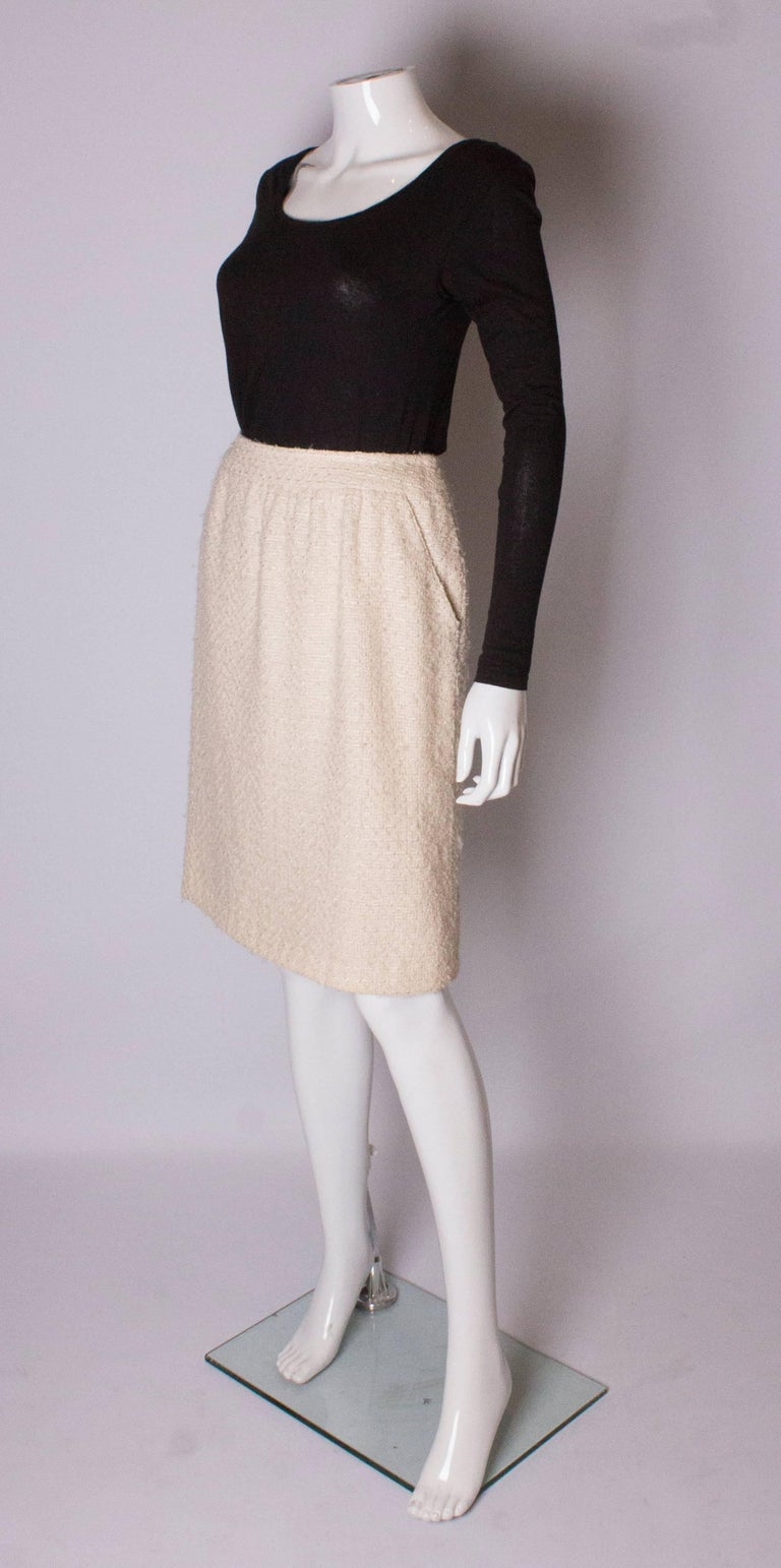 An ivory boucle skirt by Chanel  Boutique. The skirt is made of a wool and silk mix with a silk lining, and  has a central back zip and two  pockets at the front. The skirt has a 4'' hem.