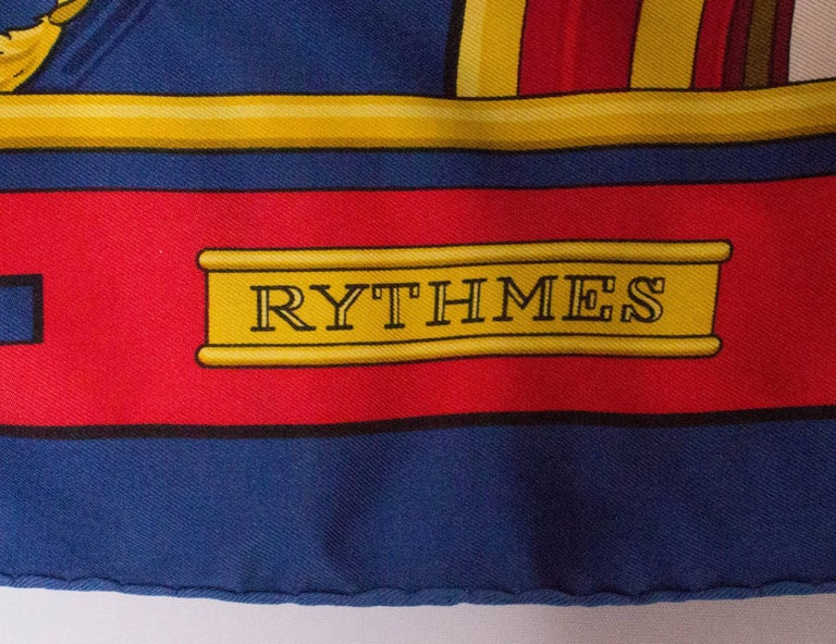 A chic silk scarf by Hermes. Rythmes design with a blue border, and red, gold and blue design.