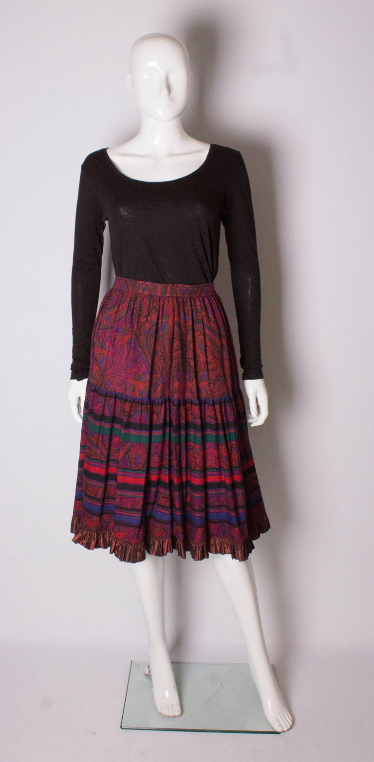 Yves Saint Laurent Rive Gauche paisley print skirt in a wonderful colour palete of pinks and and purples.The skirt has one pocket on either side and a satin frill at the hem.