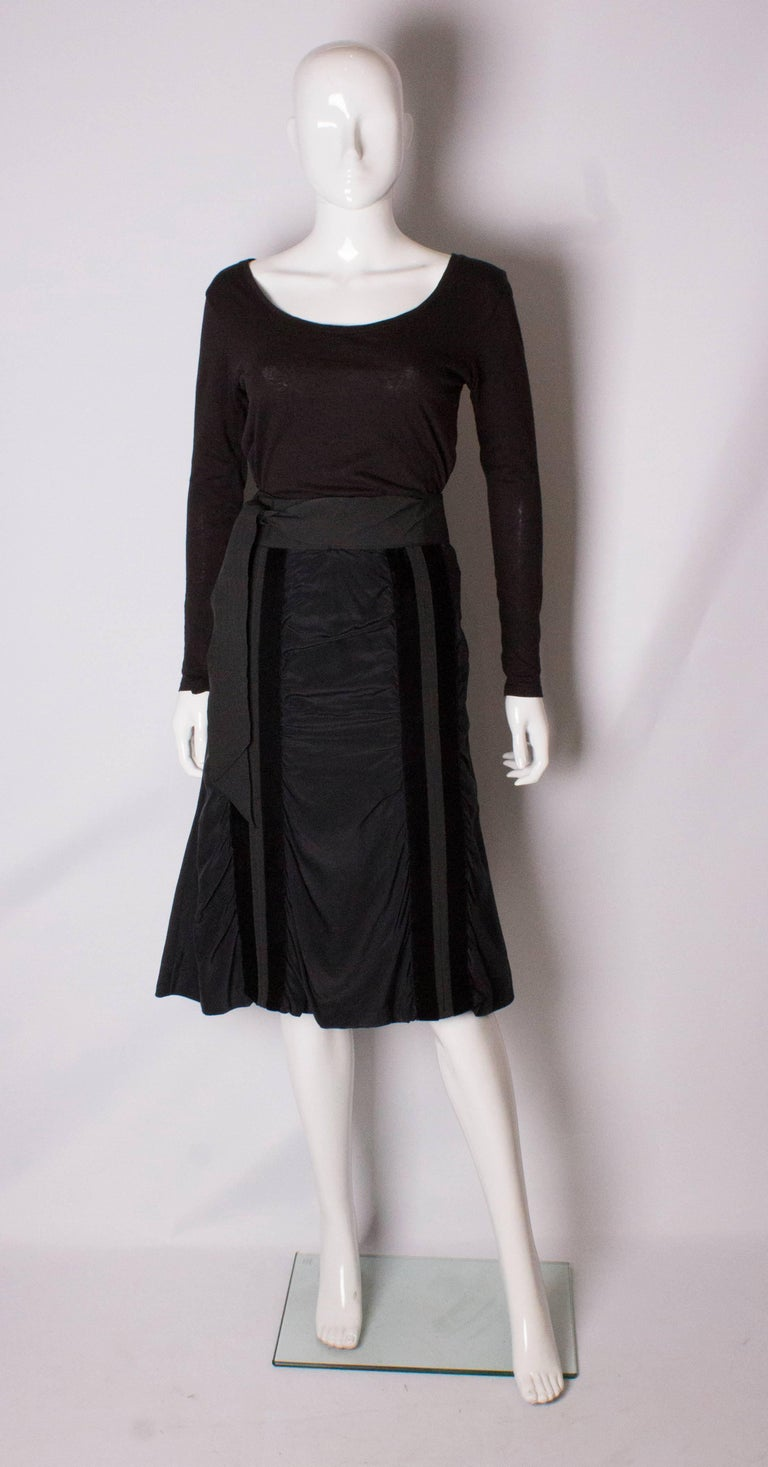 A super silk skirt by Yves Saint Laurent Rive Gauche line. The skirt is made of silk , and is lined in silk. It has a central back zip and vertical velvet stripe on the front and back, with a grossgrain self tie belt. It has never been worn.