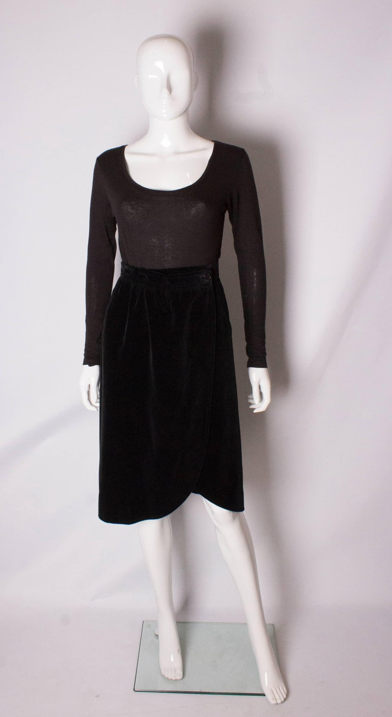A chic black velvet wrap around skirt by Yves Saint Laurent , Variation line. The skirt is fully lined and has a pocket on the right hand side.