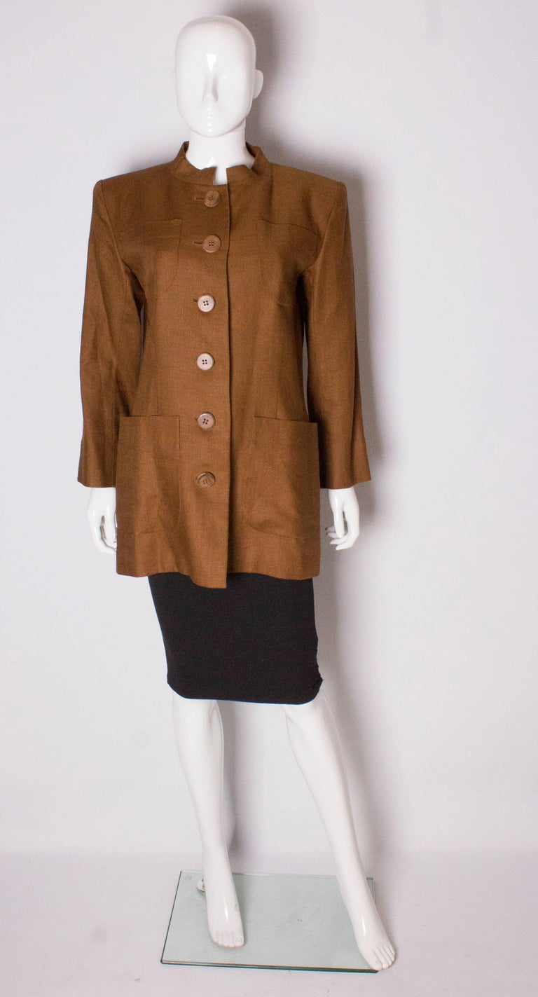 A chic jacket for Spring, from Yves Saint Laurent , Rive Gauche line. In an mid brown linen, the jacket has 2 breast pockets and 2 pockets at waist leval. It has a 6 wooden button opening at the front, one button on each cuff and a stand up