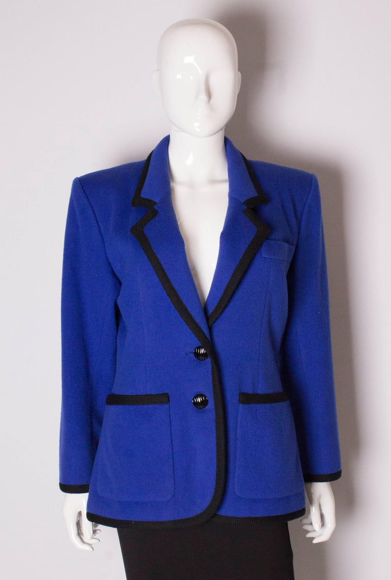 A chic and warm jacket by Yves Saint Laurent , Rive Gauche. The jacket is in a royal blue wool with black braid trim around the edge and cuffs. It has 1 breast pocket, 2  large pockets on the front , and a two button fastening with 2 buttons on each